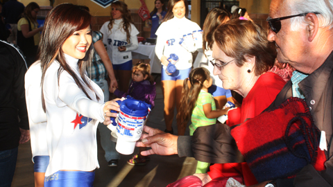 A 66ers Dance Team member distributes a promotional item at the ballpark in 2010.